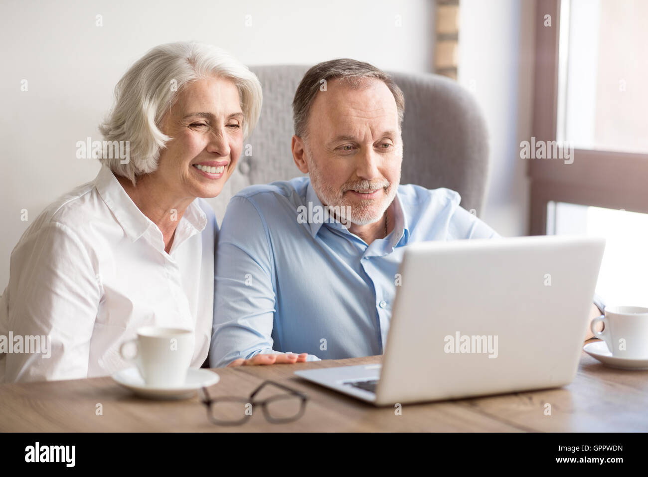Positive couple sitting at the table - Stock Image