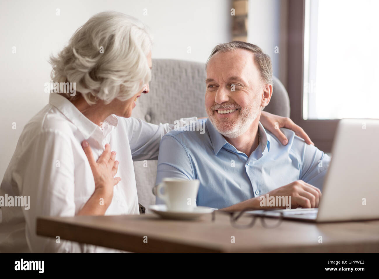 Cheerful couple sitting at the table - Stock Image
