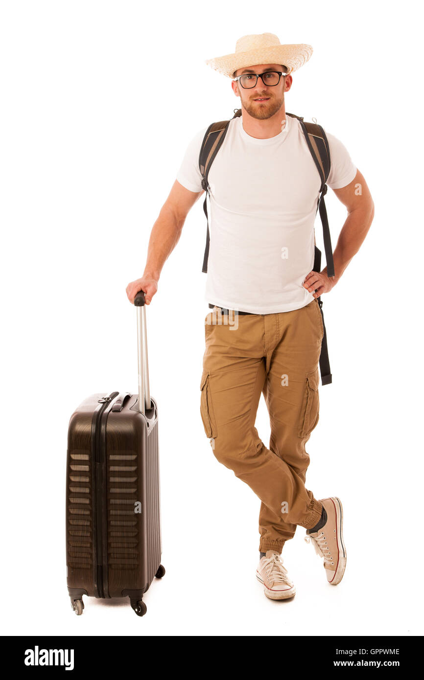 Traveler with straw hat, white shirt, backpack and suitcase waiting for transport isolated. - Stock Image