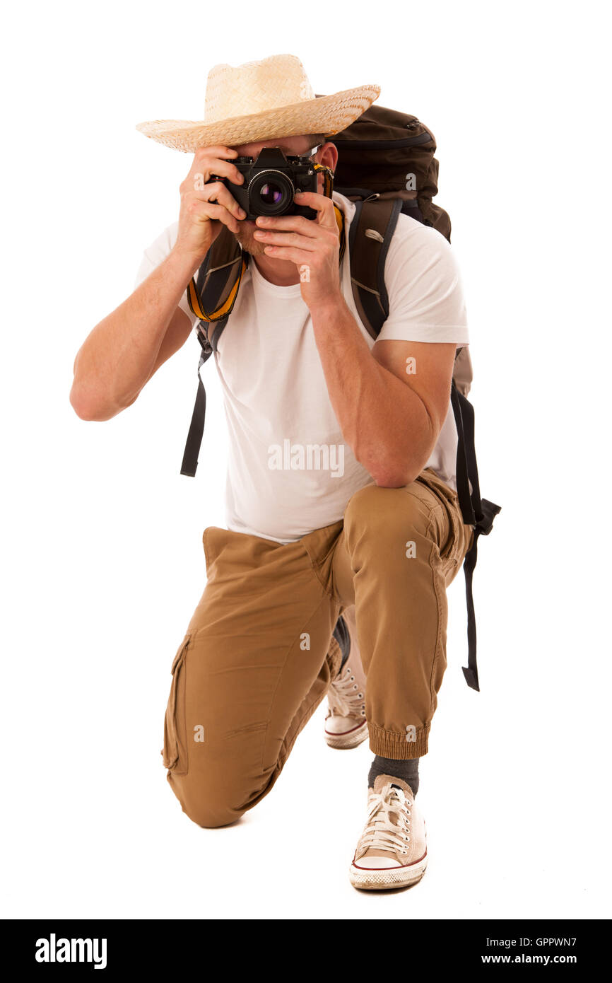 Traveler with straw hat, white shirt, backpack and photo camera exploring new world isolated. - Stock Image