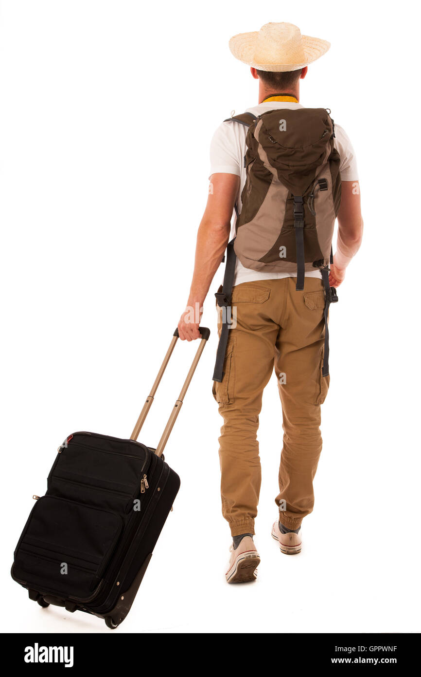 Traveler with straw hat, white shirt, backpack and suitcase walking away isolated. - Stock Image