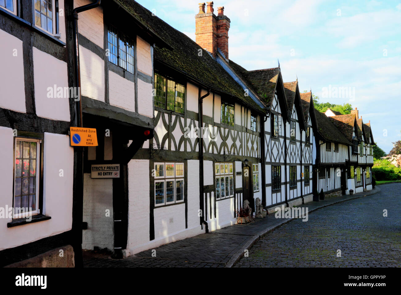 A row of half-timbered cottages in Mill Street, in the shadow of Warwick Castle. - Stock Image