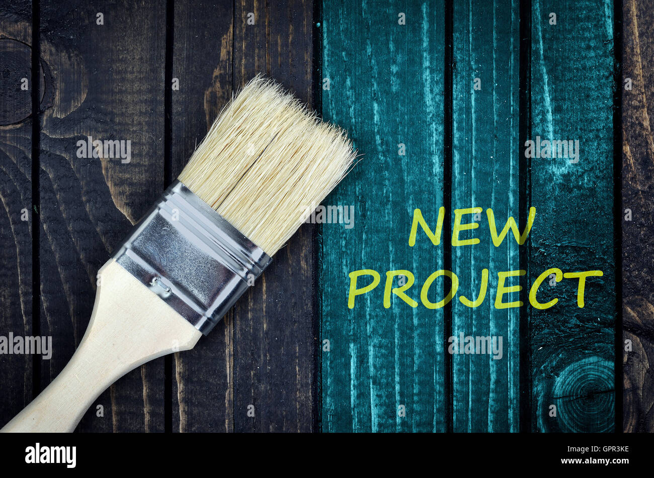 New Project message and paintbrush on wooden wall - Stock Image