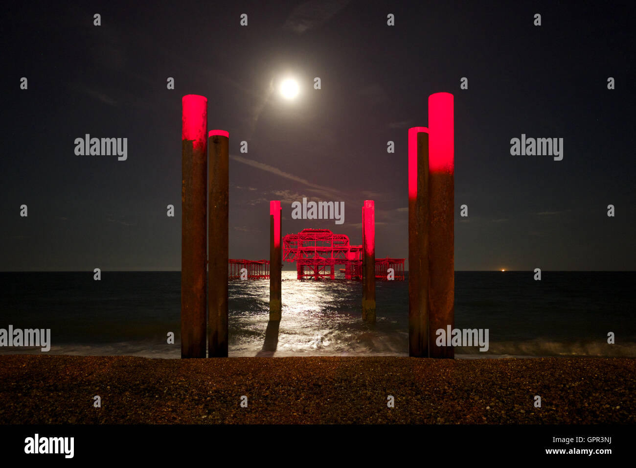 Brighton Beach, West Pier and the sea lit by moonlight with a red beam of light projected onto the pier - Stock Image