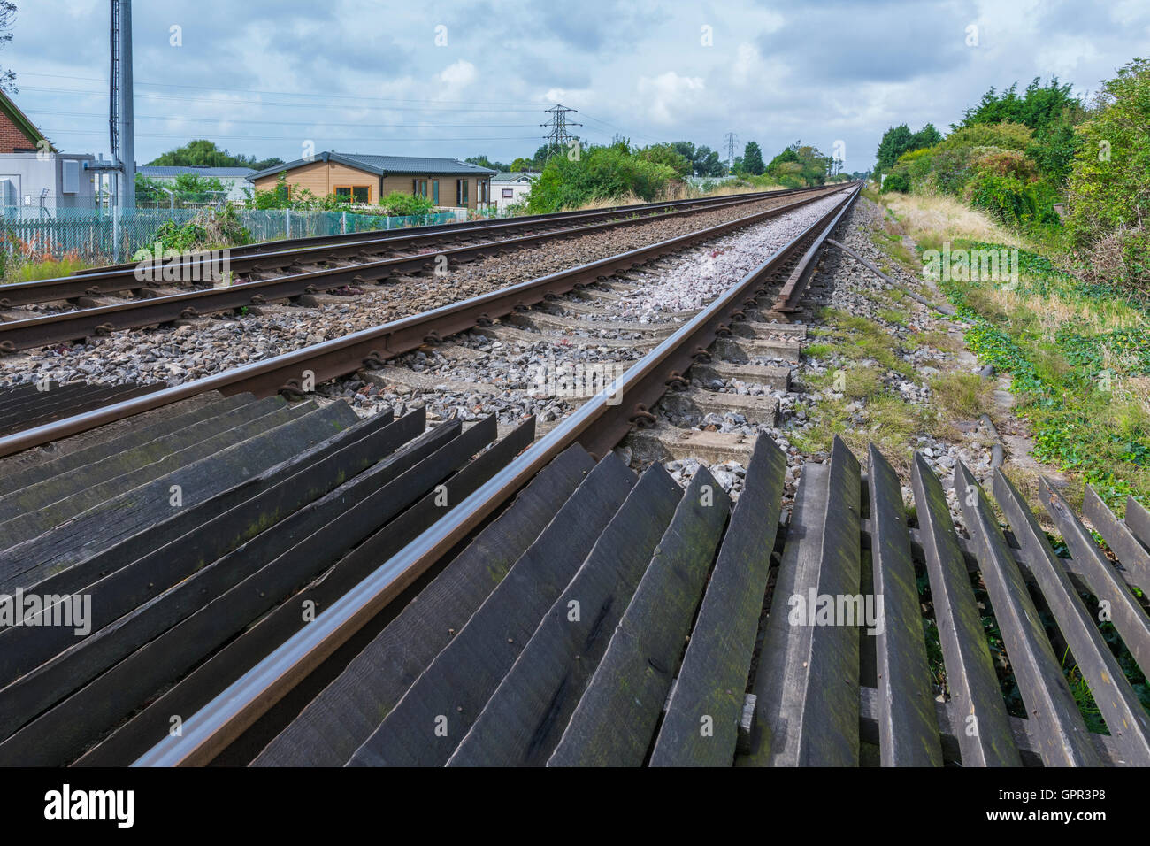 Railway tracks from low perspective looking along the track, in the UK, taken from a public pedestrian crossing. - Stock Image