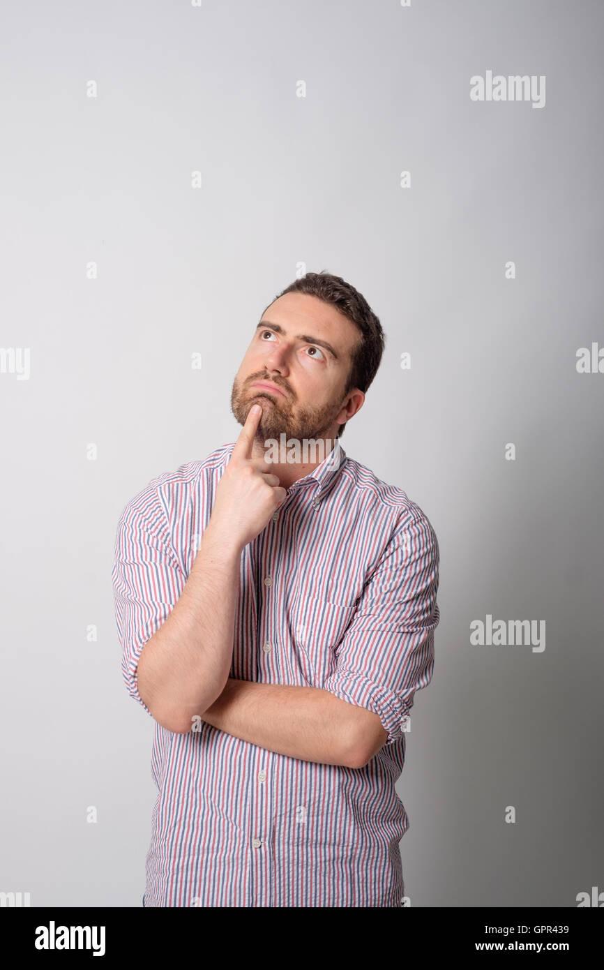 Doubtful man on gray background - Stock Image