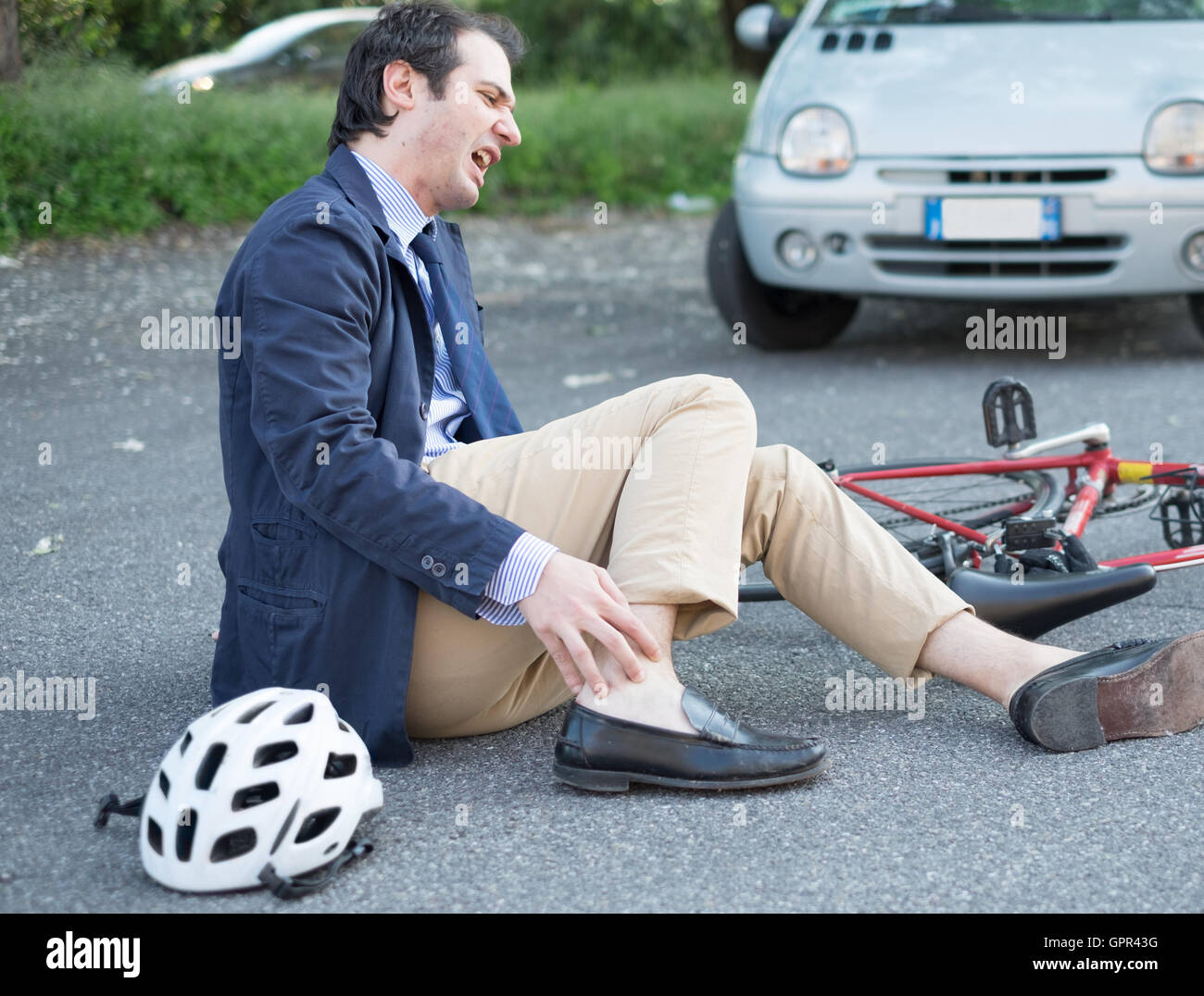 aching man after bicycle accident on the asphalt - Stock Image