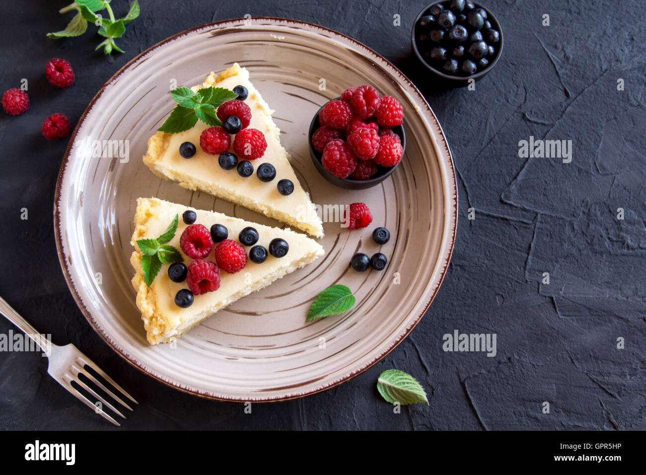 Homemade cheesecake with fresh berries and mint for dessert - Stock Image