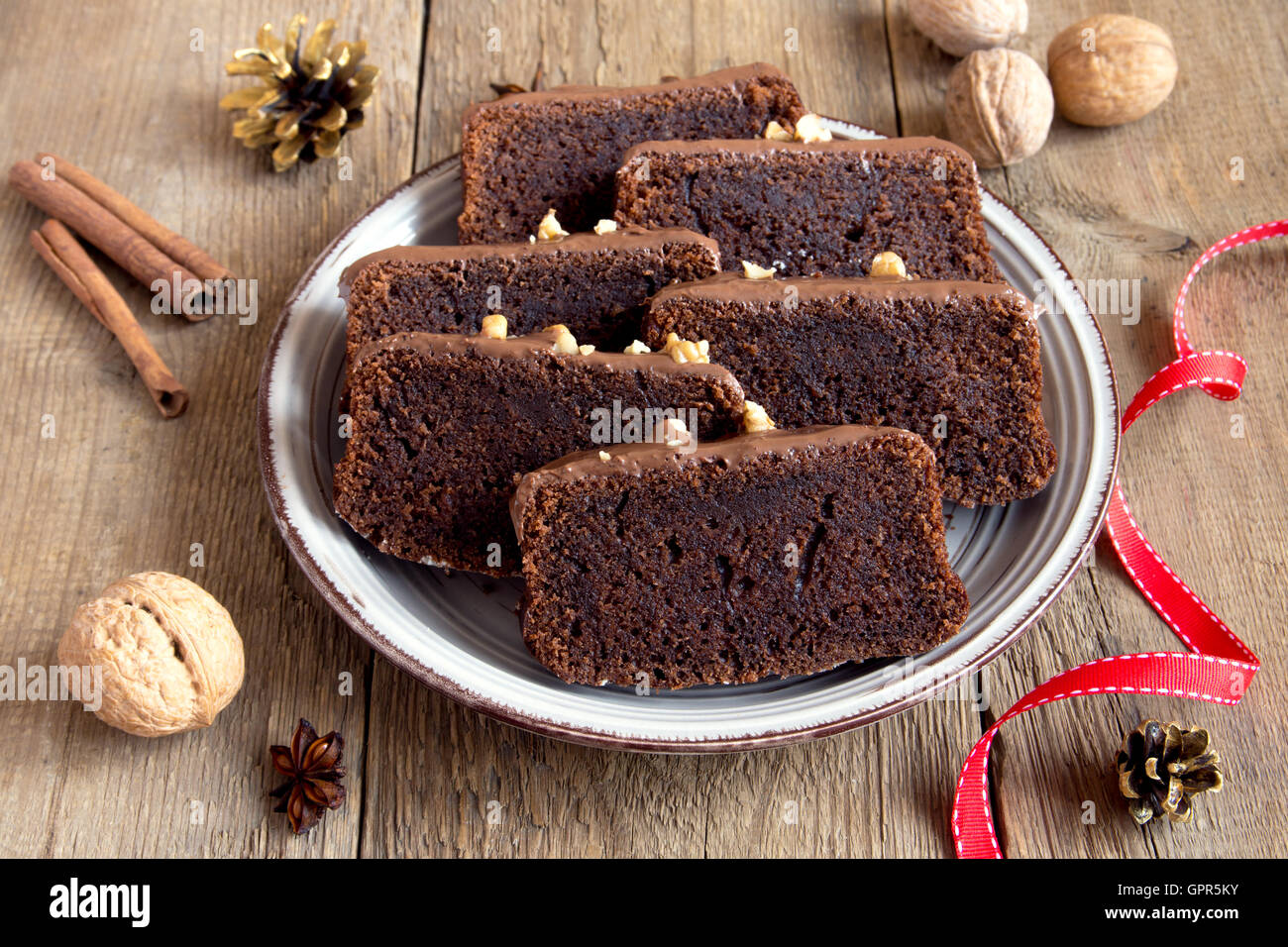 Chocolate sliced cake with nuts and spices for Christmas over rustic wooden background - Stock Image