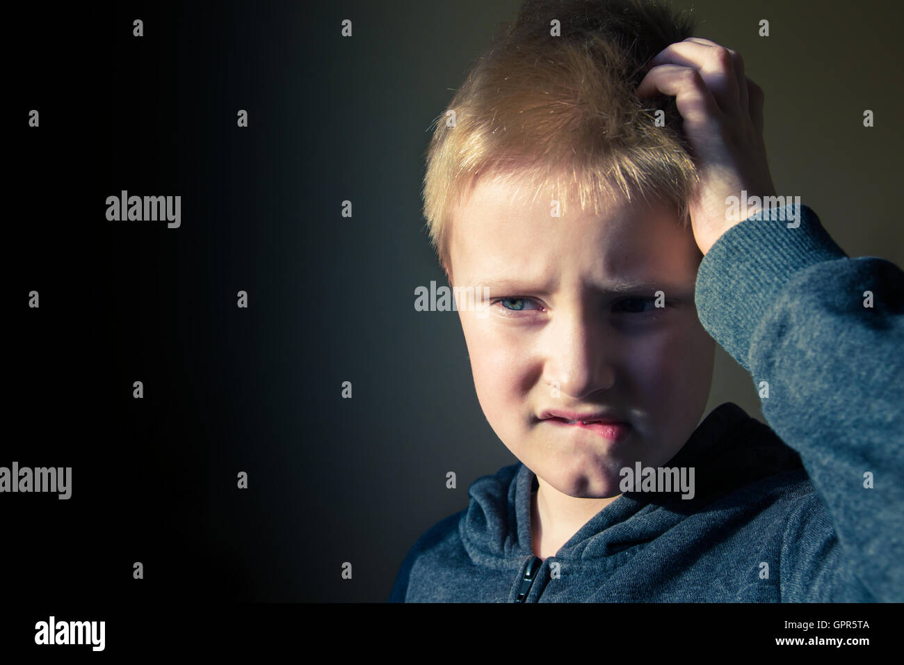 Boy (teen, kid) scratching head confused in trouble over dark background with copy space - Stock Image