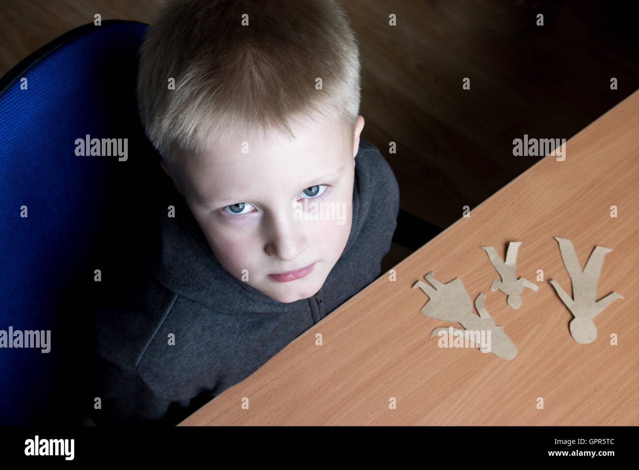 Confused child with broken paper family, family problems, divorce, custody battle, suffer concept - Stock Image
