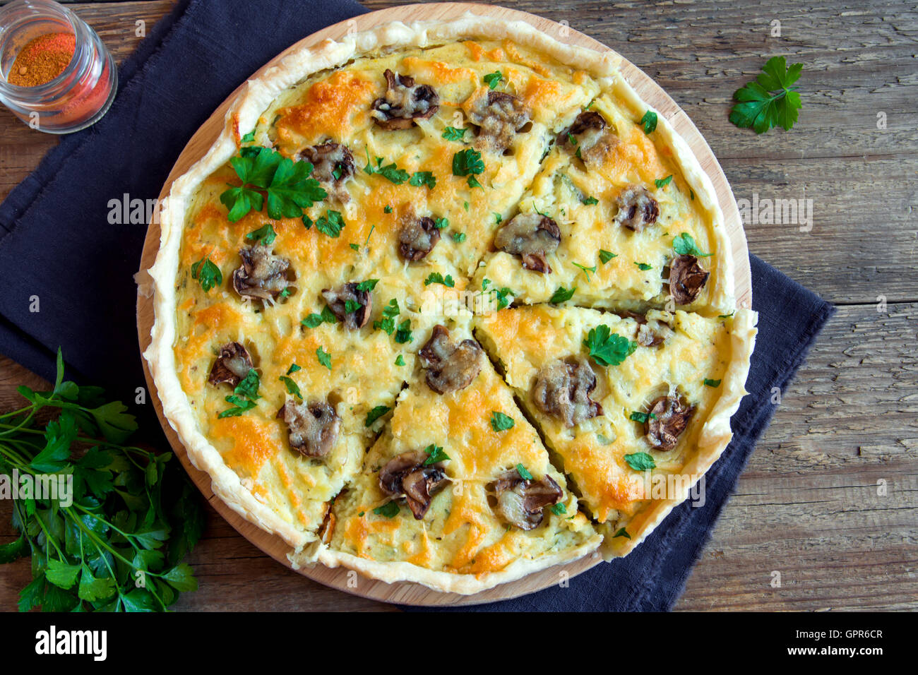 Homemade french quiche pie with mushrooms (champignons) and cheese over rustic wooden background - Stock Image