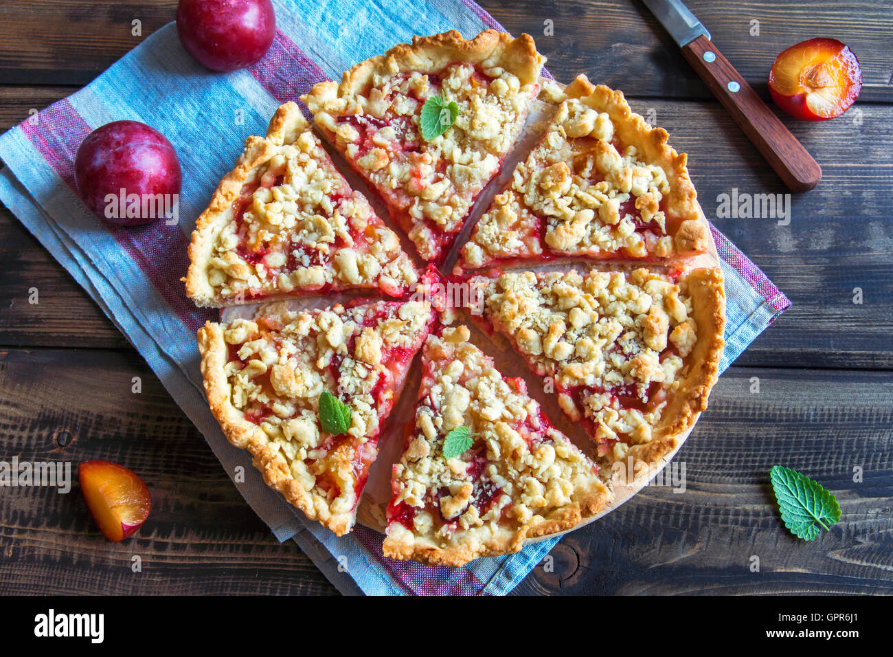 Homemade shortcrust plum cake with crumble on wooden background - Stock Image