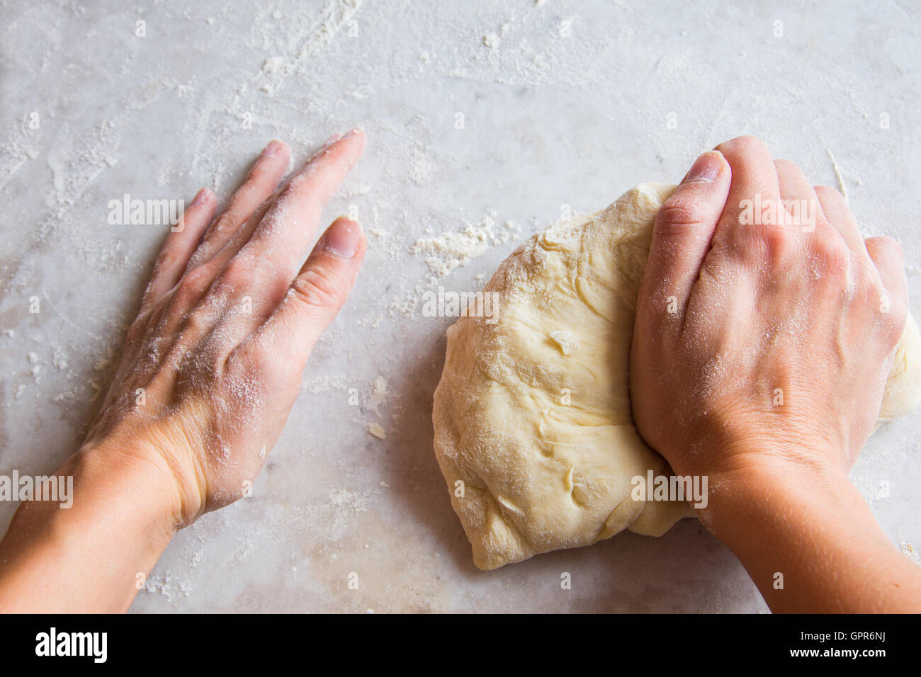 Hands kneading dough on white table Stock Photo