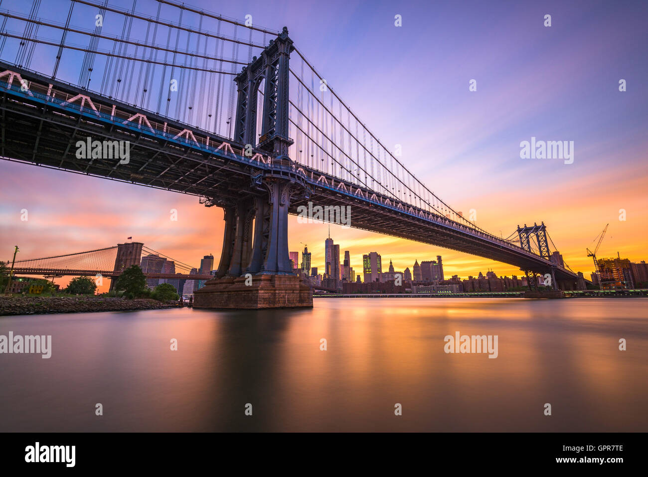 New York City at the Manhattan Bridge spanning the East River during sunset. - Stock Image