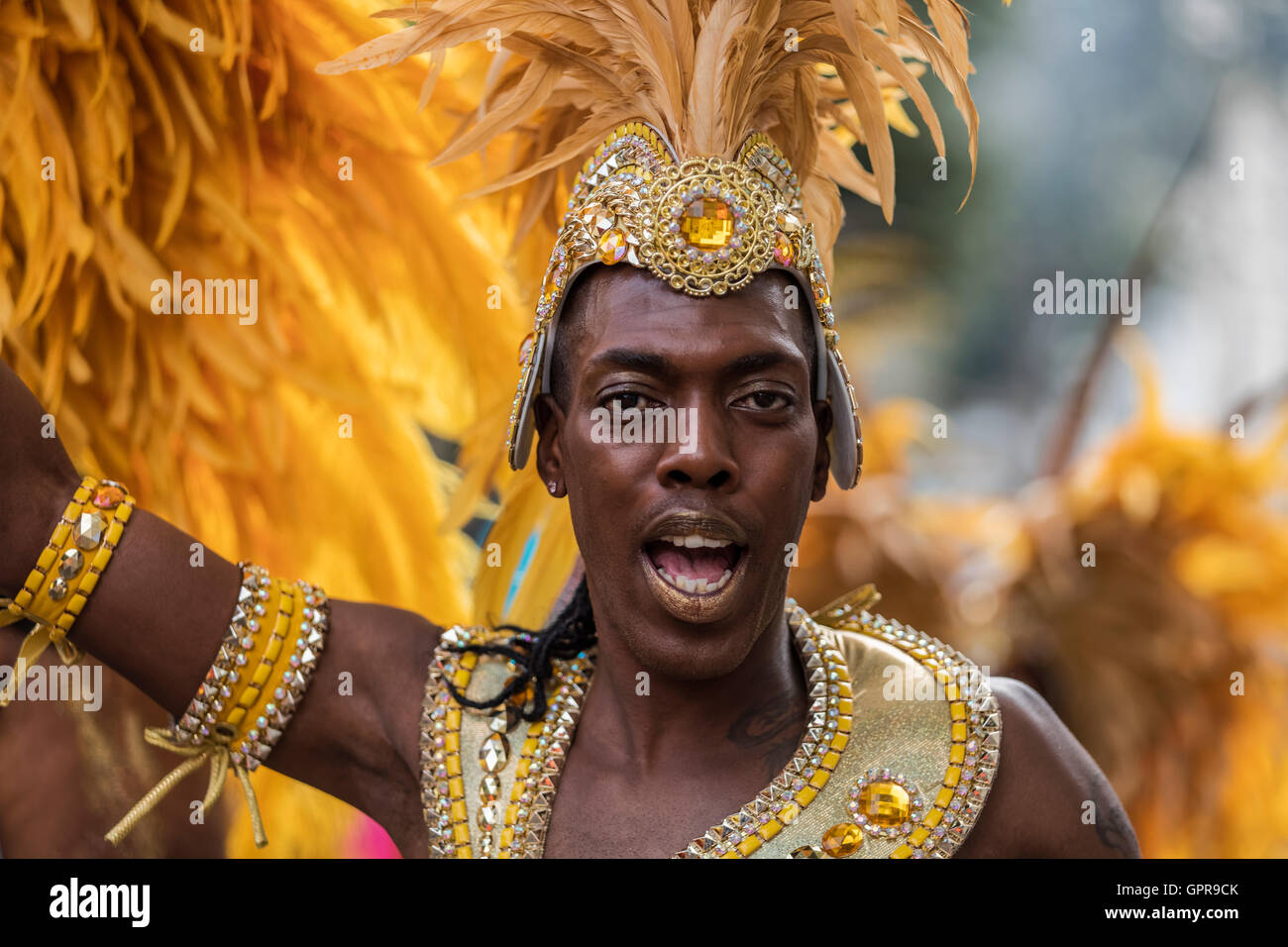 Afro Caribbean black man in costume with a yellow feather headdress at the Notting Hill carnival in West London - Stock Image