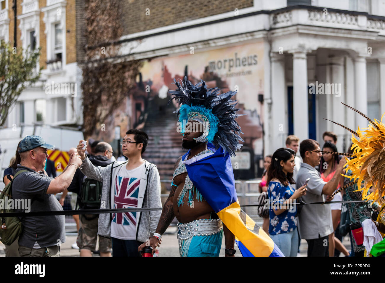 black african man walking in Ladbroke grove during the Notting Hill carnival parade in West London - Stock Image