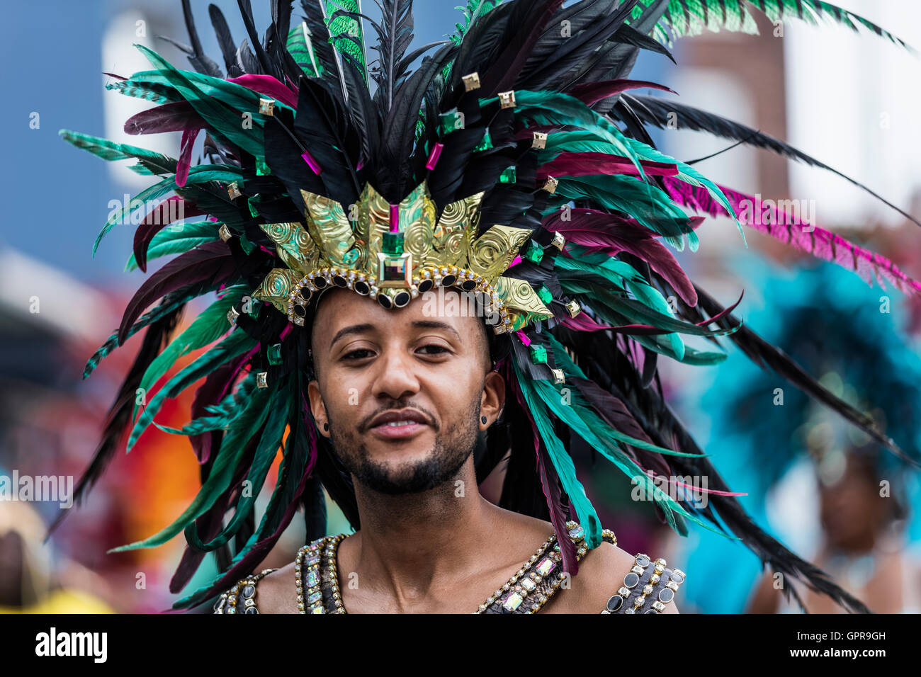 Black African man with a colourful black turquoise and green feather headdress at the Notting Hill Carnival in West - Stock Image