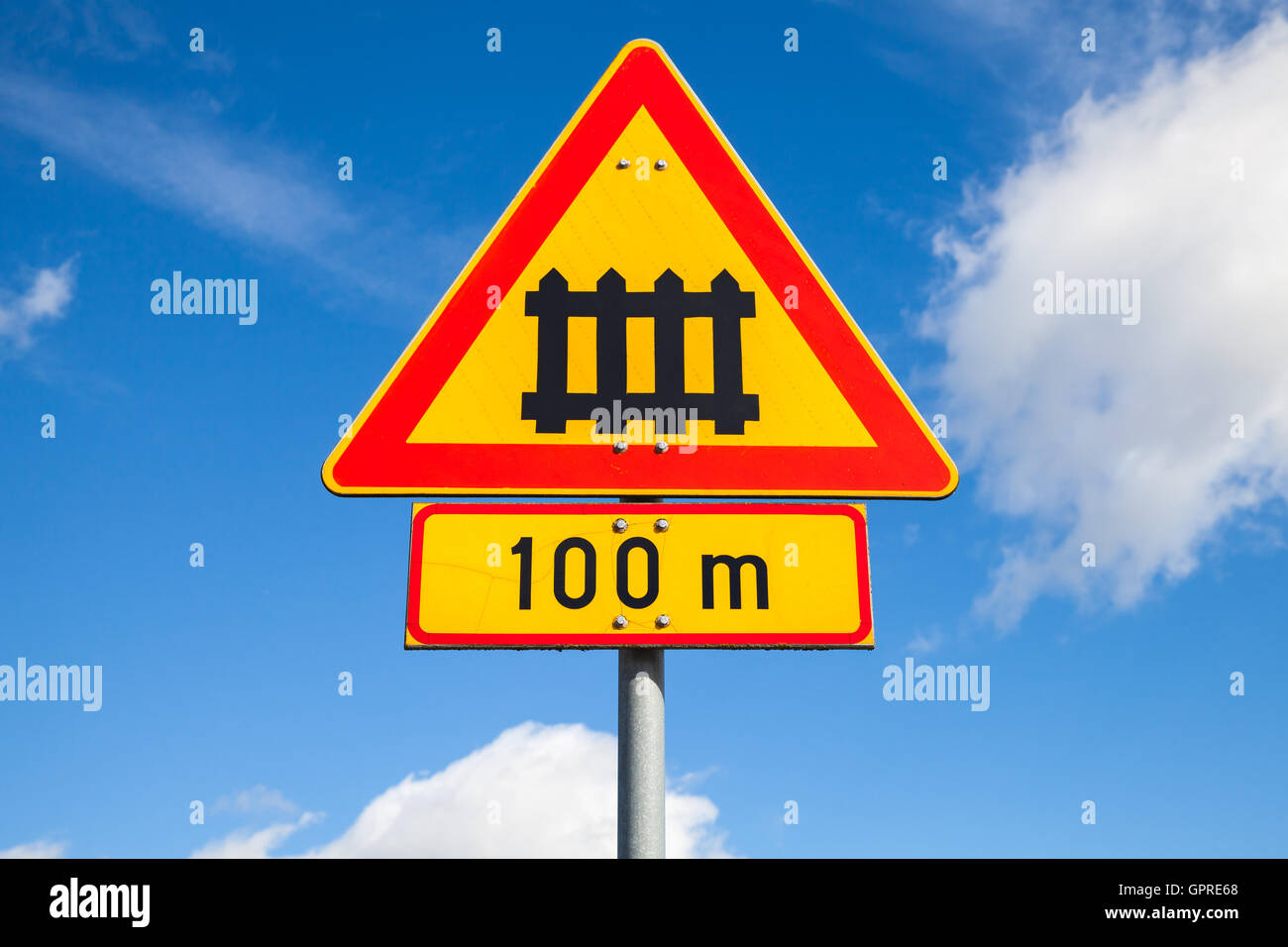 Sweden railway crossing with gate sign. Triangular warning roadsign with red border and 100m distance label over - Stock Image