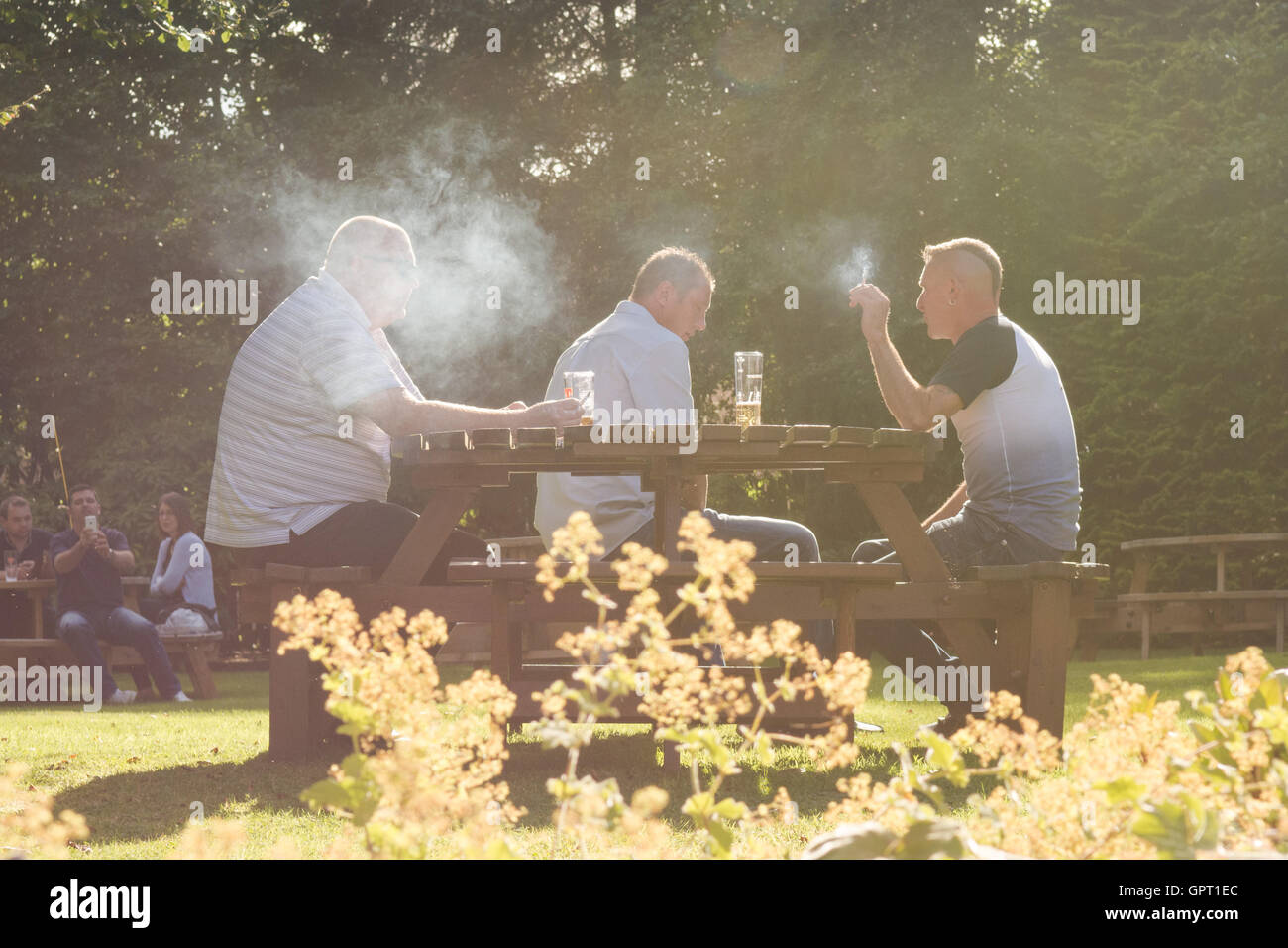 Smokers in a pub beer garden in Scotland, UK, surrounded by smoke - Stock Image