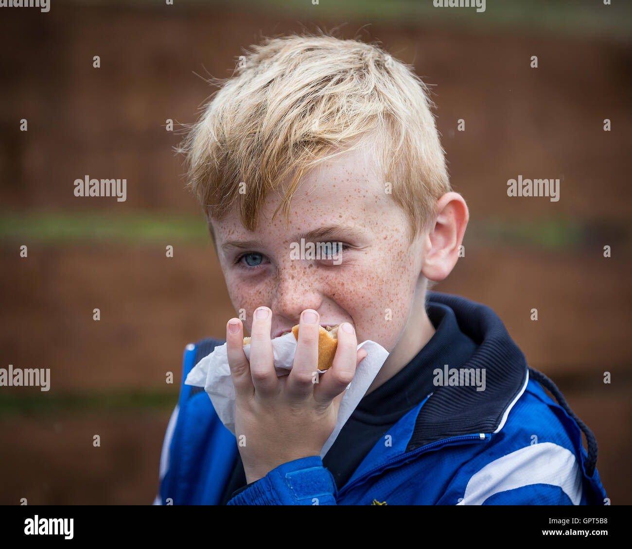 Young, smiling, blond boy holding and eating a pie with one hand - Stock Image