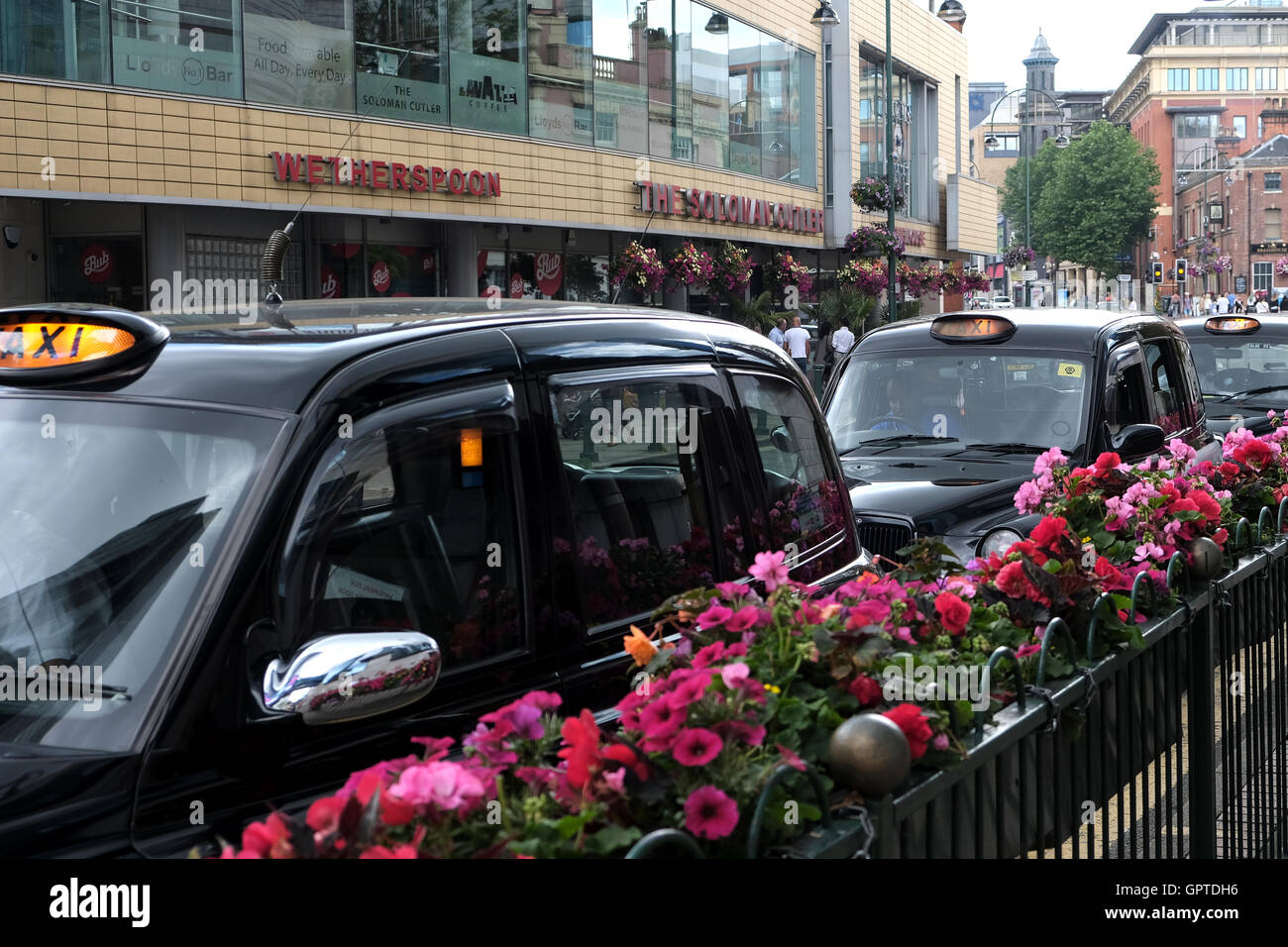 A row of black cabs, taxis, with illuminated signs waiting for customers on a busy High st Stock Photo