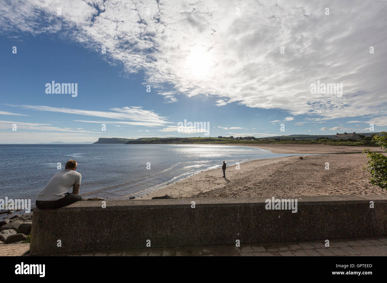 Man observing the sandy beach of Ballycastle, County Antrim, Northern Ireland, United Kingdom - Stock Image