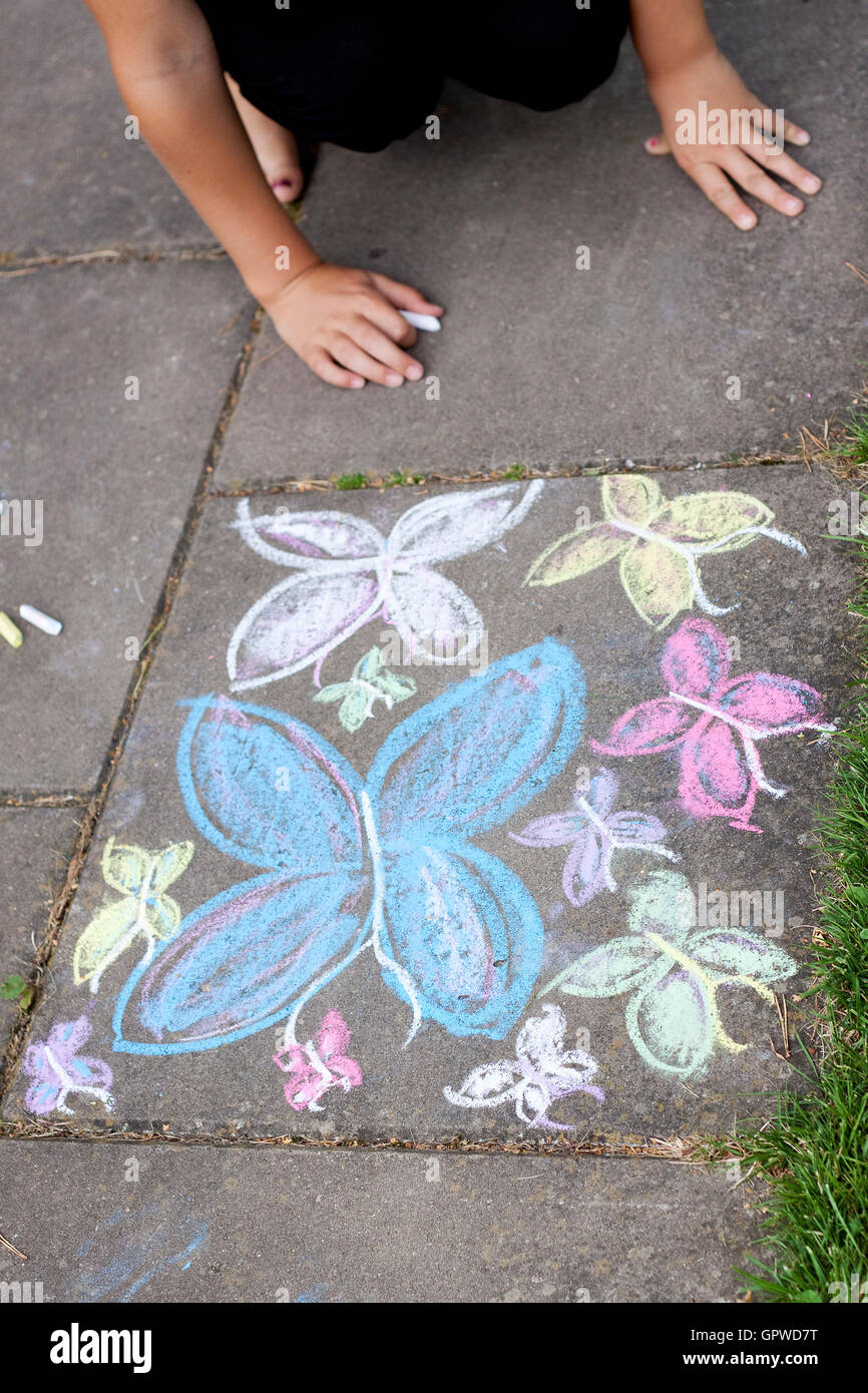 Chalk drawing of butterflies on sidewalk - Stock Image