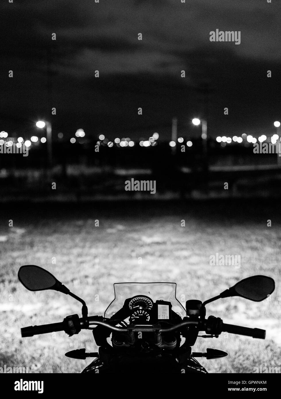 A motorcycle looks out over the night sky of Baltimore - Stock Image
