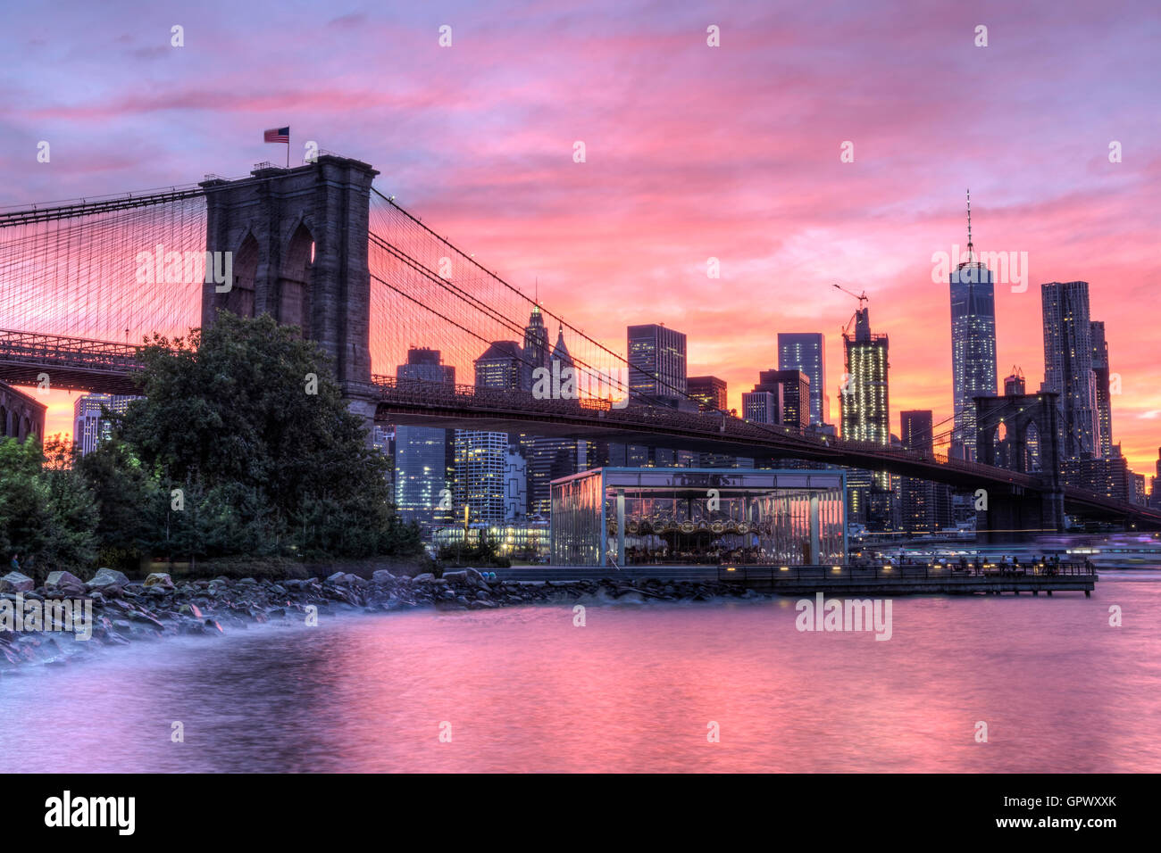 A colorful twilight view of the Brooklyn Bridge and the Manhattan skyline see from Empire Fulton Ferry Park in Brooklyn, - Stock Image