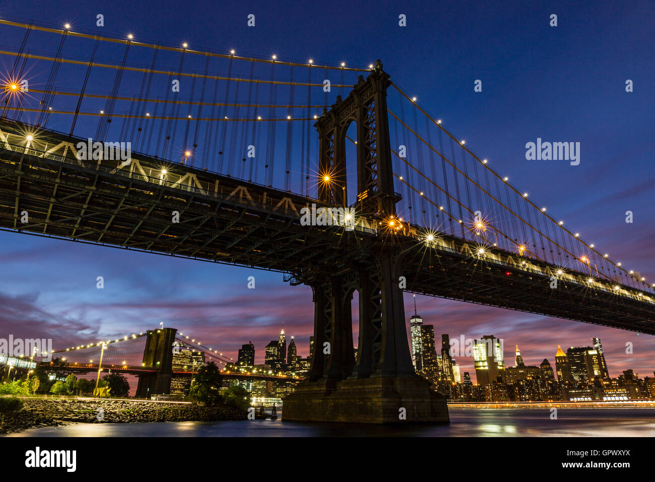 A colorful twilight view of the Manhattan and Brooklyn Bridges, and the Manhattan skyline see from John Street Park, - Stock Image