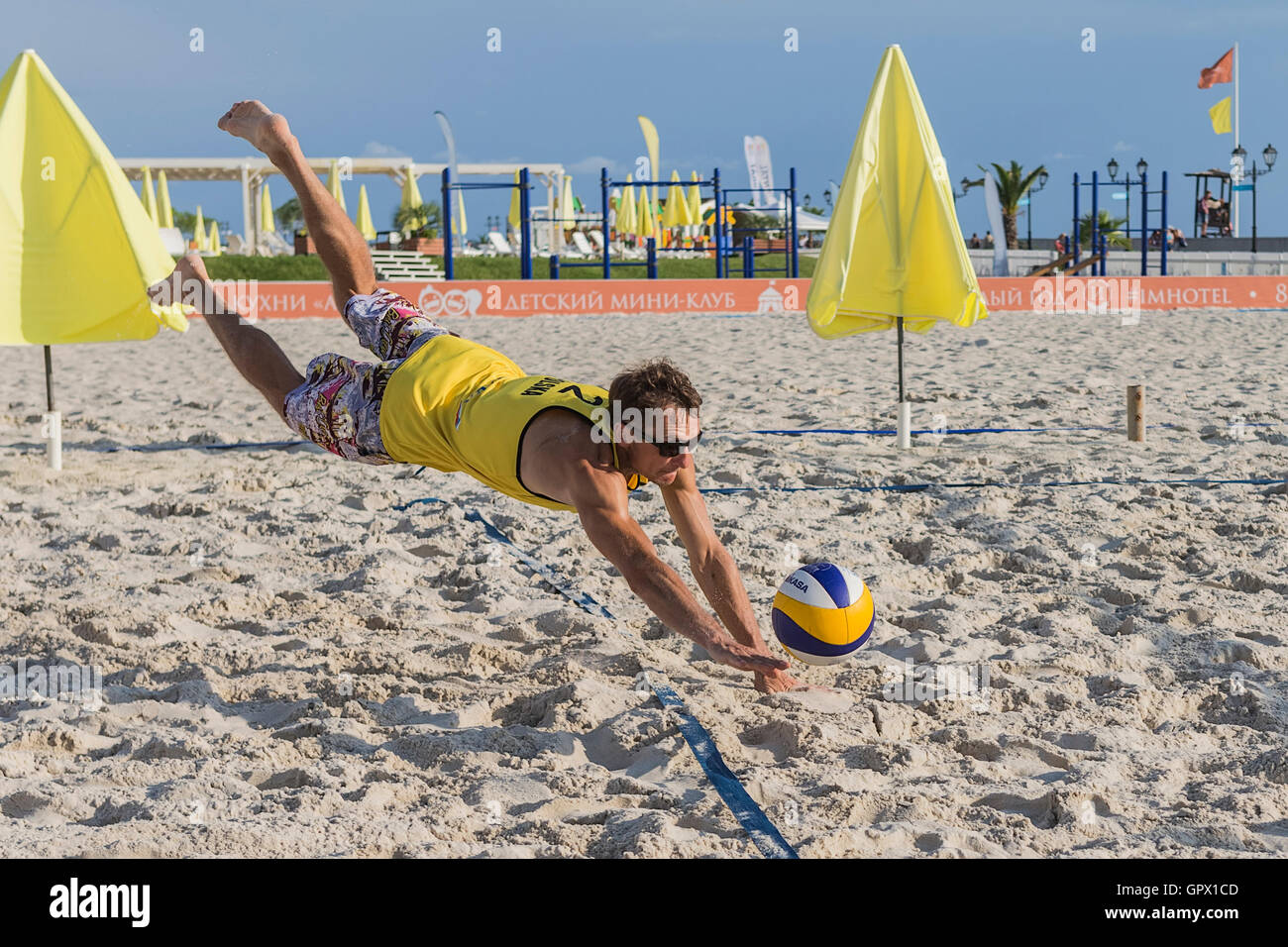 Young man in motion plays in beach volleyball. - Stock Image