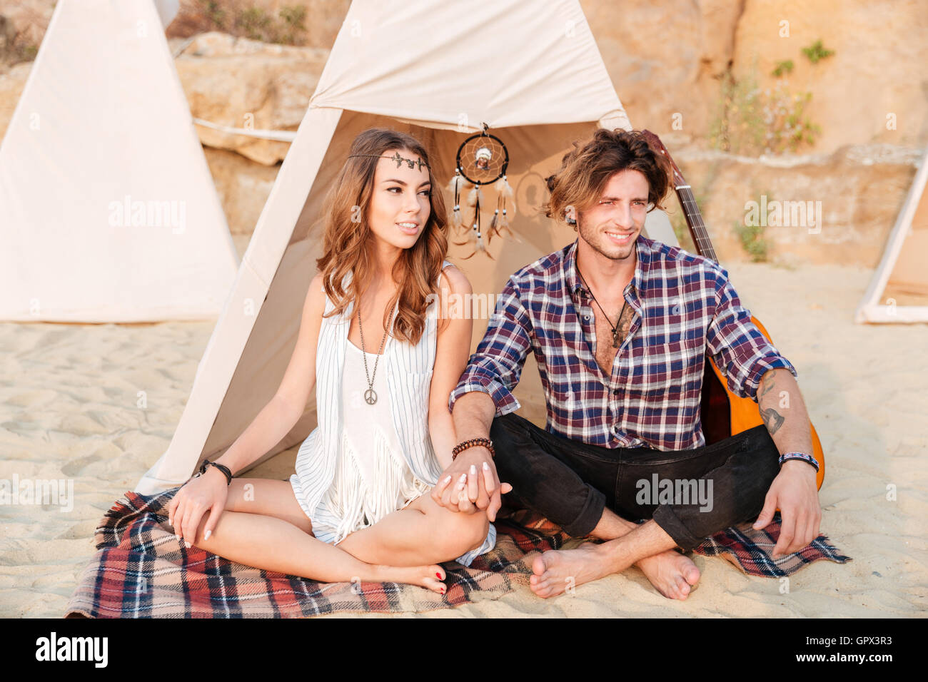 Young beautiful smiling hippie couple sitting with legs crossed at the beach near tent - Stock Image