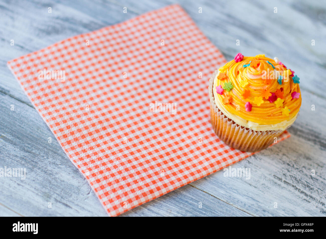 Cupcake on red checkered napkin. - Stock Image