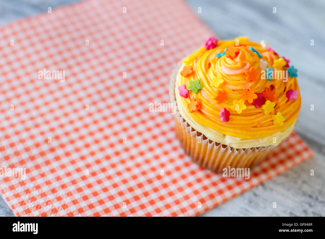 Cupcake with orange icing. - Stock Image