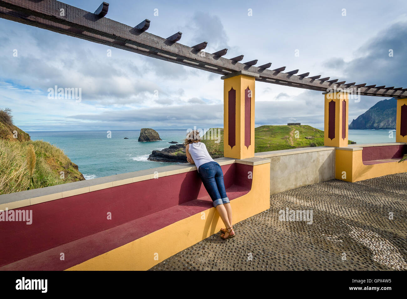 Woman looking at the ocean from special viewpoint spot in Porto da Cruz, Madeira. - Stock Image