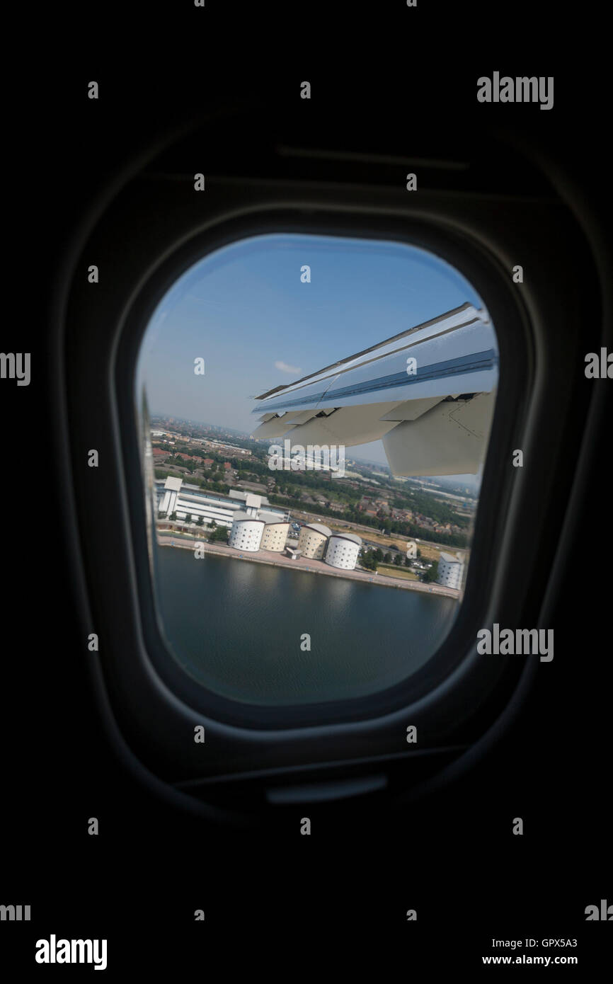 A view out of the window of a passenger jet flying over the Royal Albert Dock in London, shortly after takeoff. - Stock Image