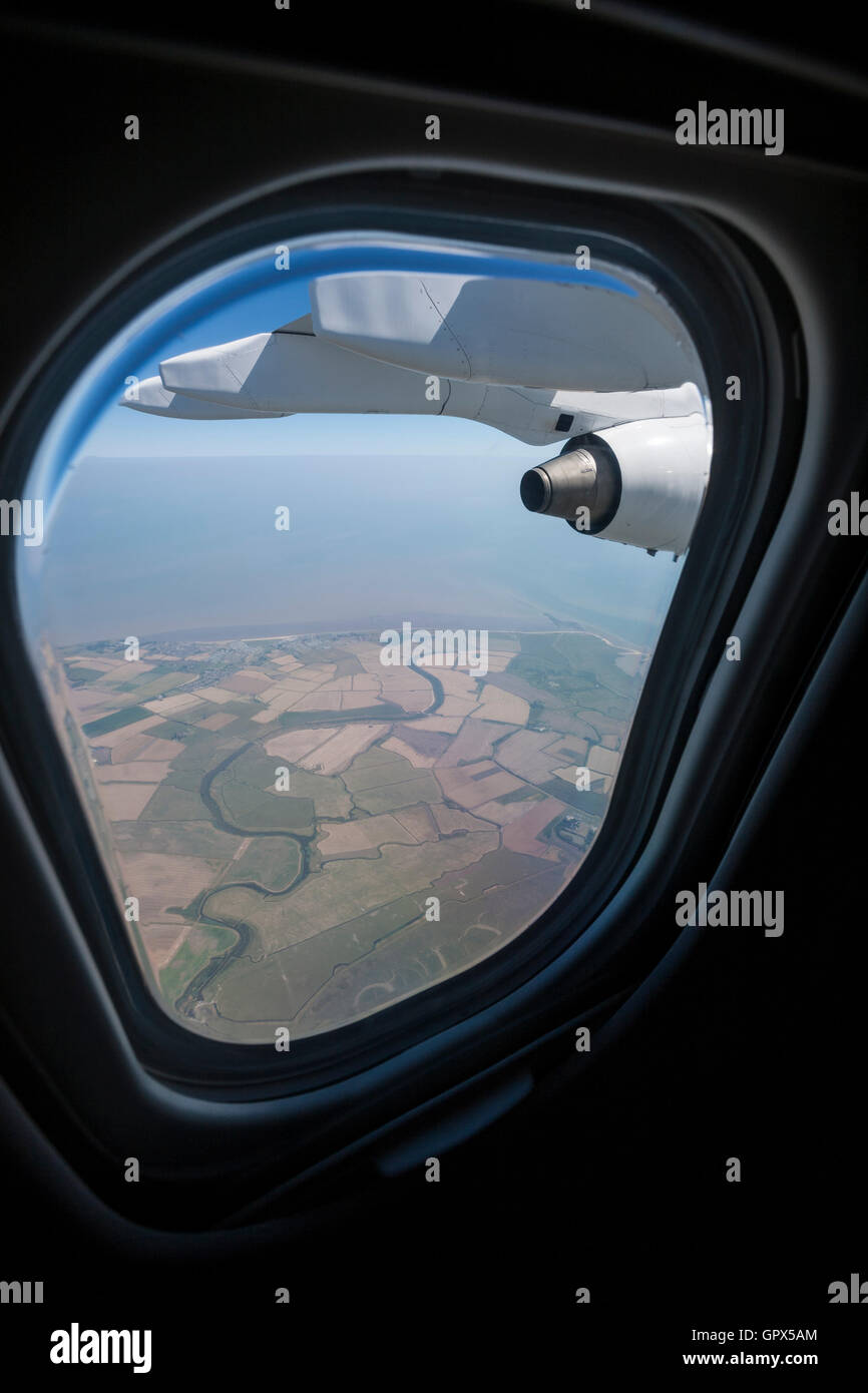 A view out of the window of a passenger jet flying over the Thames Estuary in England. - Stock Image