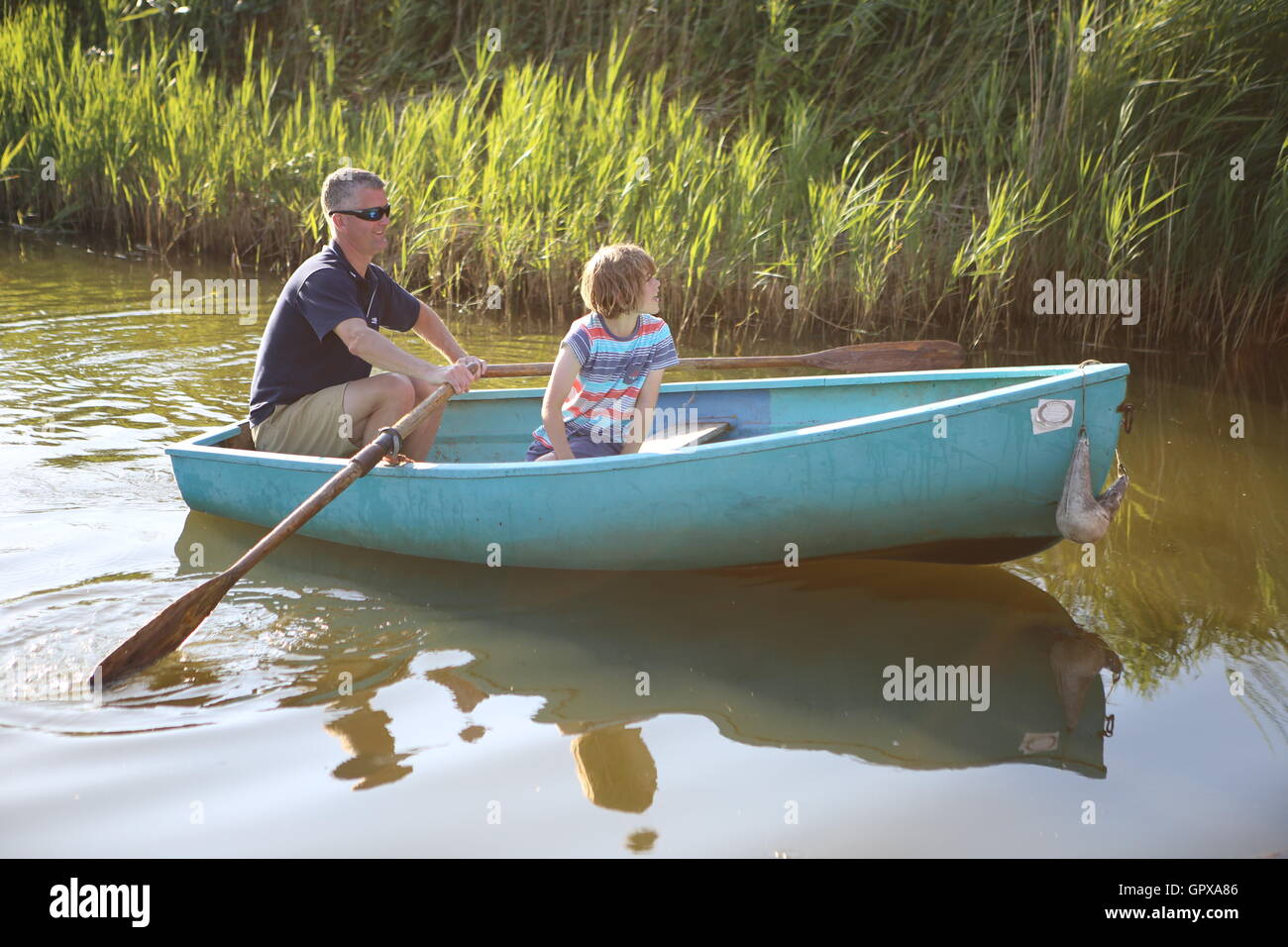 Man and child in rowing boat Norfolk broads UK - Stock Image