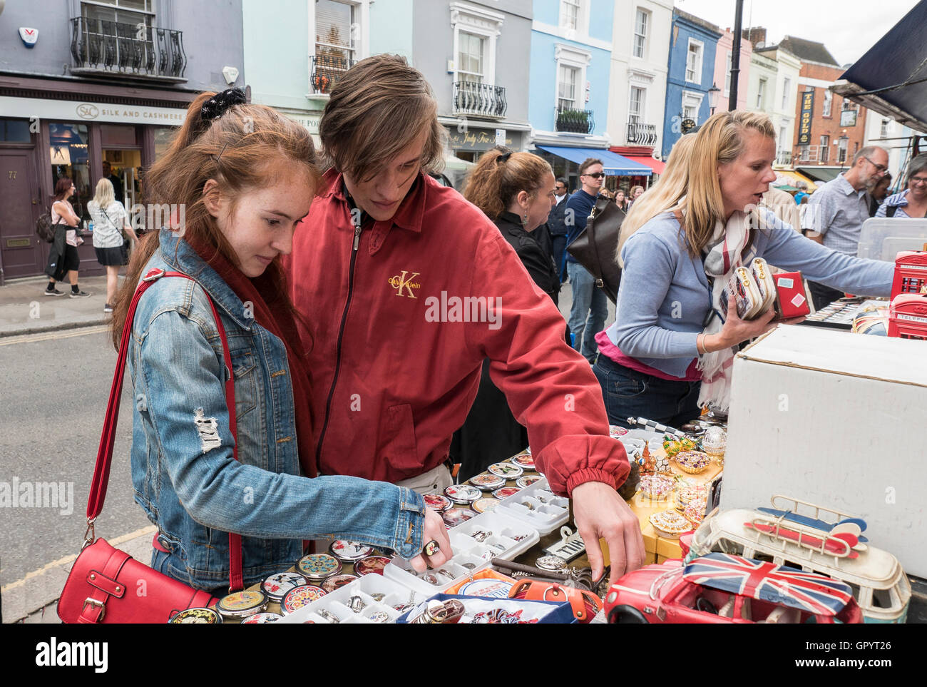 Buying souvenirs at  the Portobello Road Market in London Notting Hill Gate W11 - Stock Image
