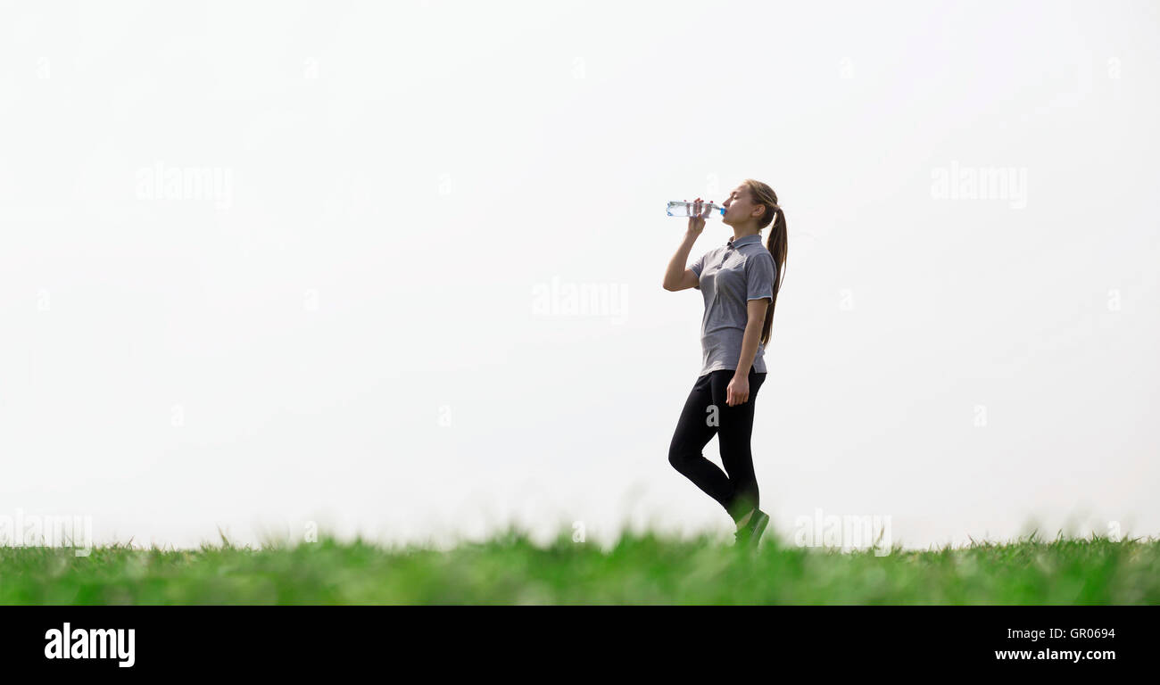 Woman drinking natural water in green field. Concept of health, thirst, hot weather. - Stock Image