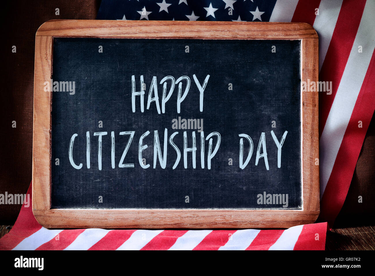 a chalkboard with the text happy citizenship day written in it and the flag of the United States, on a rustic wooden - Stock Image