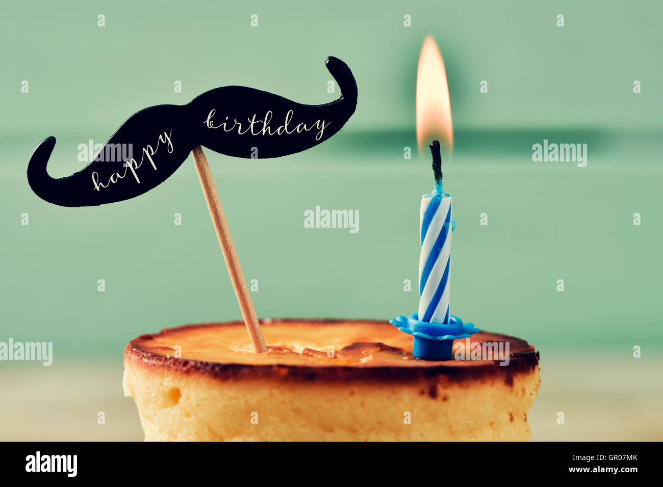 closeup of a cheesecake topped with a moustache with the text happy birthday written in it and attached to a stick, Stock Photo
