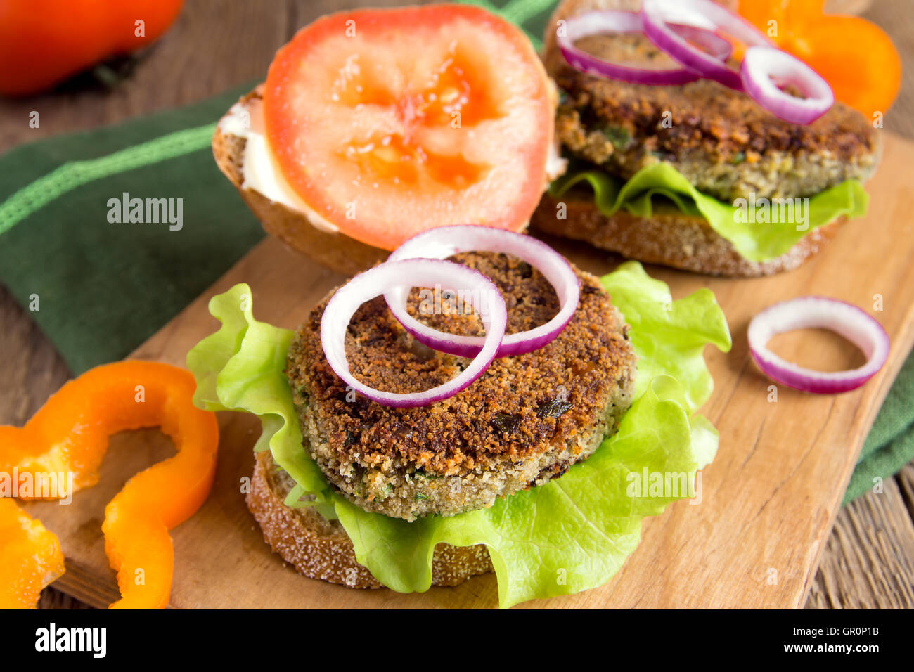 Vegetarian lentil burger with vegetables on wooden cutting board - Stock Image