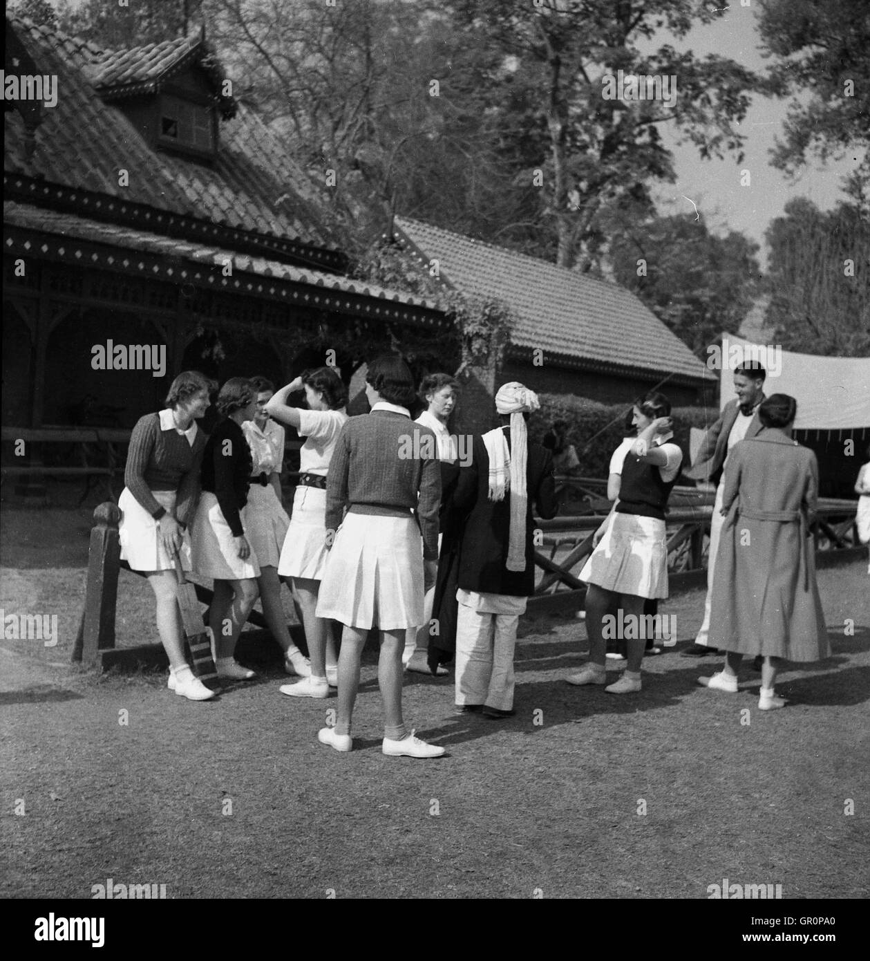 1930s, historical, local ladies cricket match in Lahore, Pakistan. Female players gather outside pavilion - Stock Image