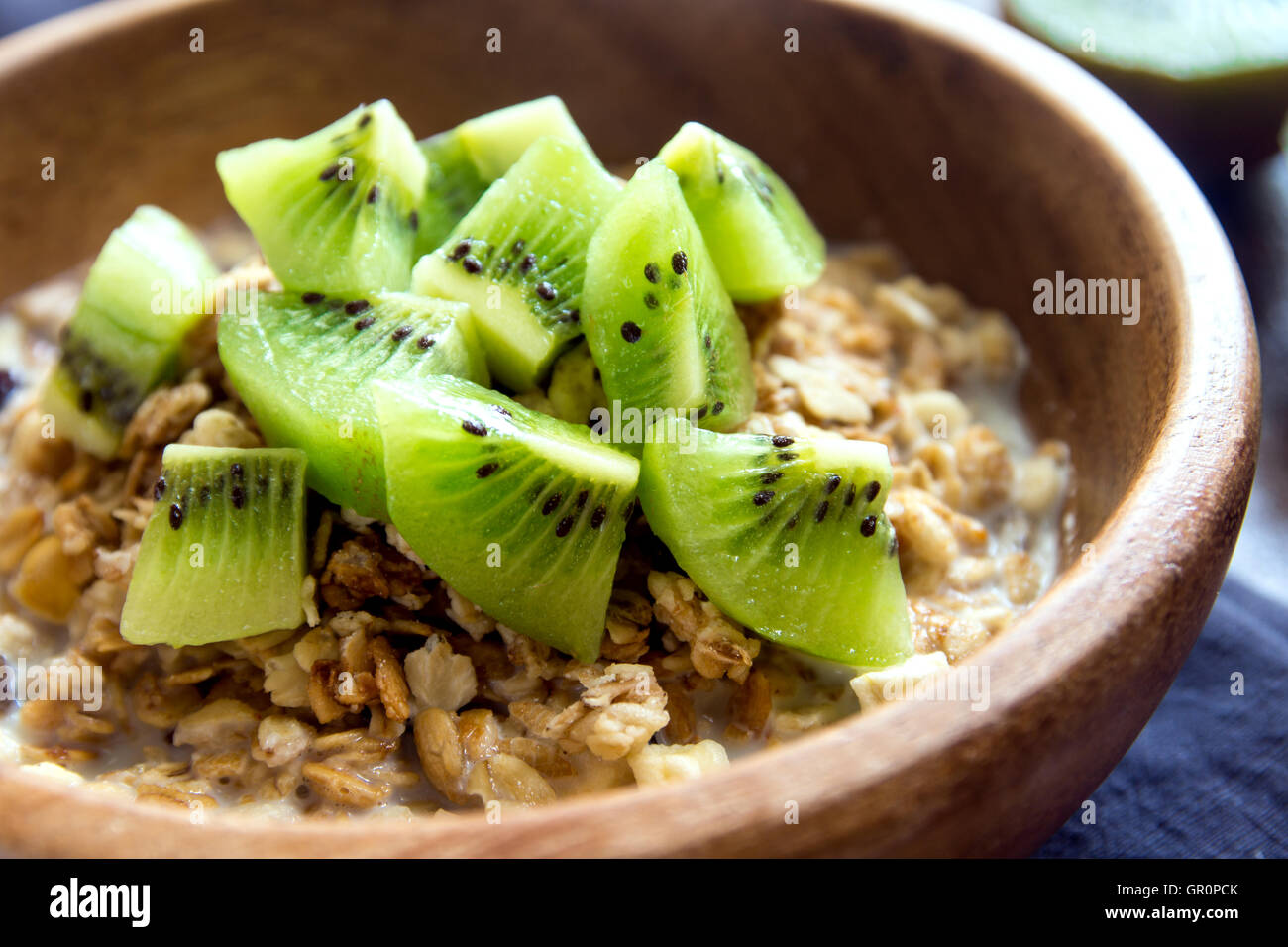 Homemade granola with milk and kiwi for healthy breakfast - Stock Image