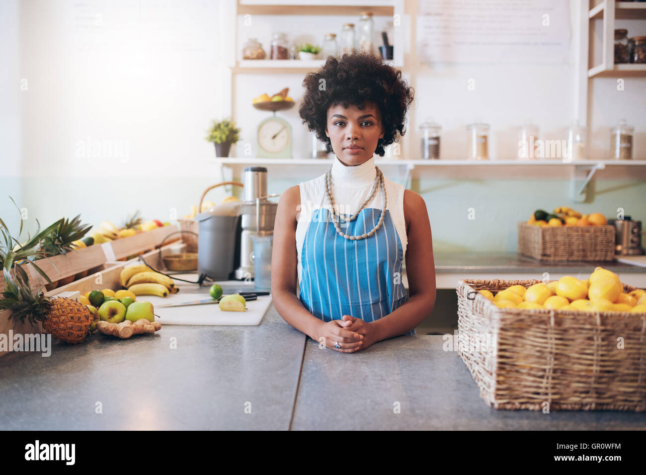 Portrait of young african woman wearing apron standing behind juice bar counter looking at camera. Stock Photo