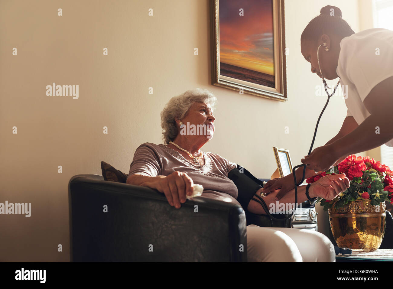 Home healthcare nurse checking blood pressure of senior woman. Elderly woman sitting on chair at home with female - Stock Image