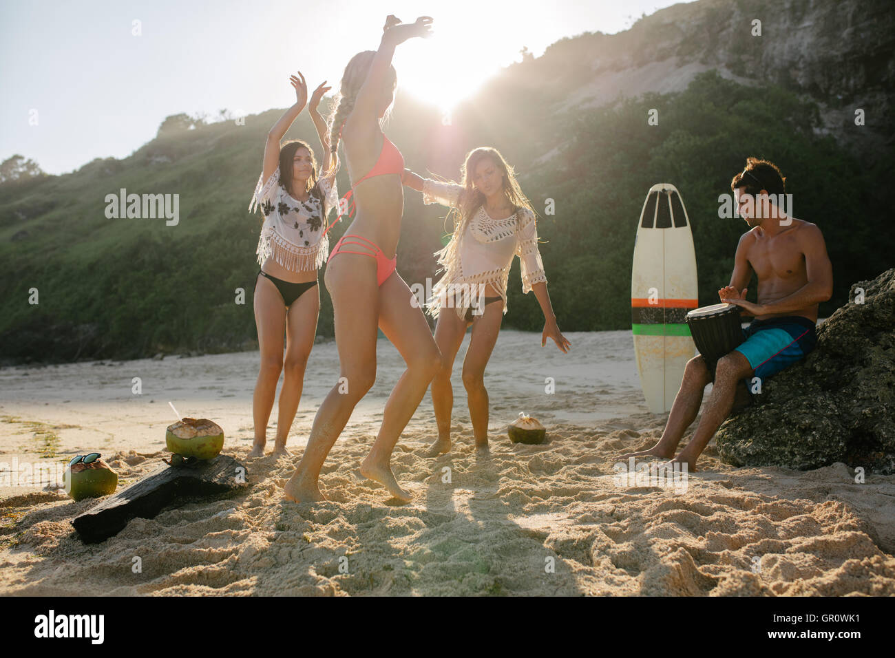 Group of young friends partying on the beach and dancing. Young people having fun at beach party, women dancing - Stock Image