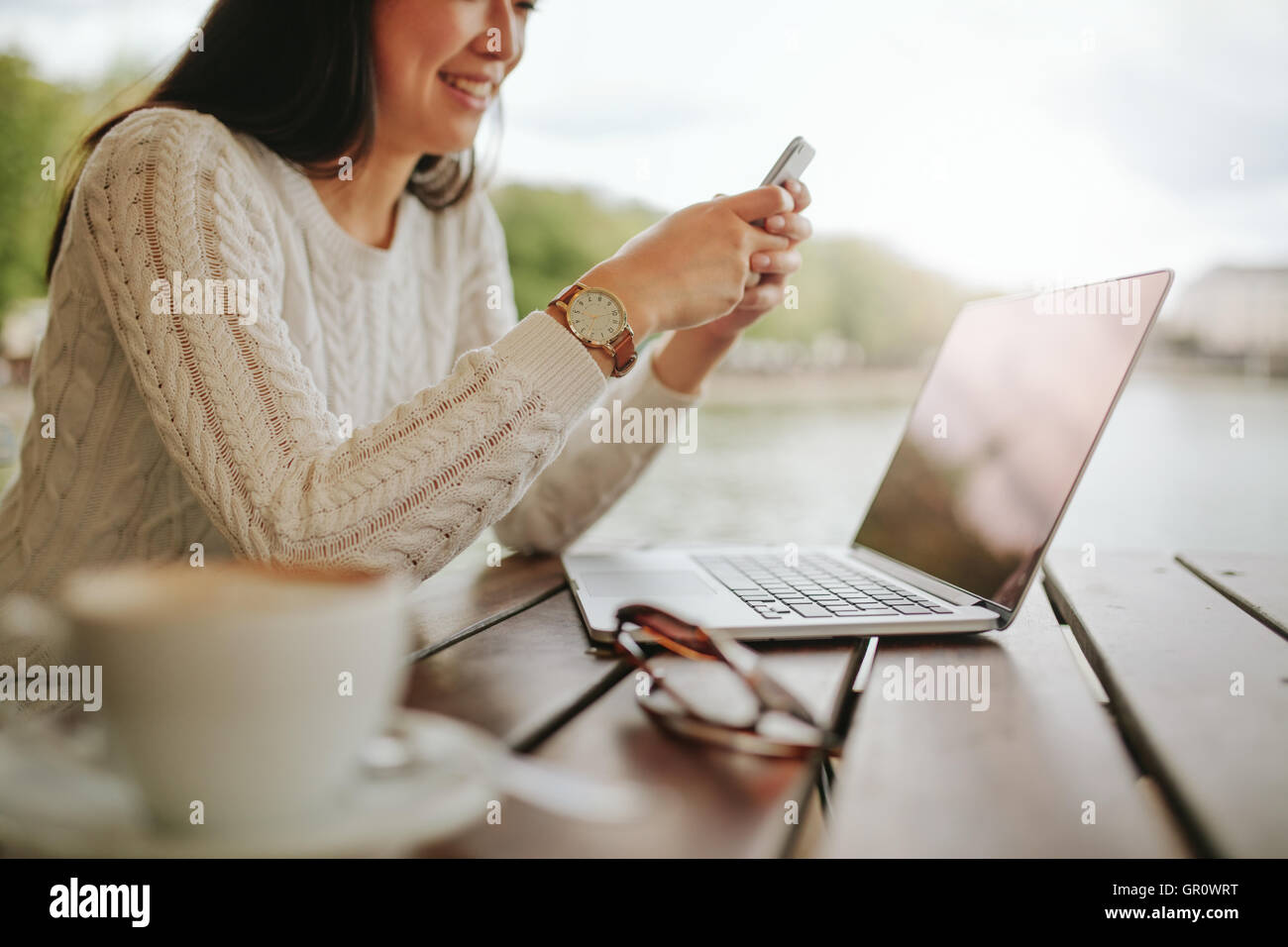 Cropped shot of young woman using mobile phone at outdoor cafe. Female sitting at table with laptop reading text - Stock Image